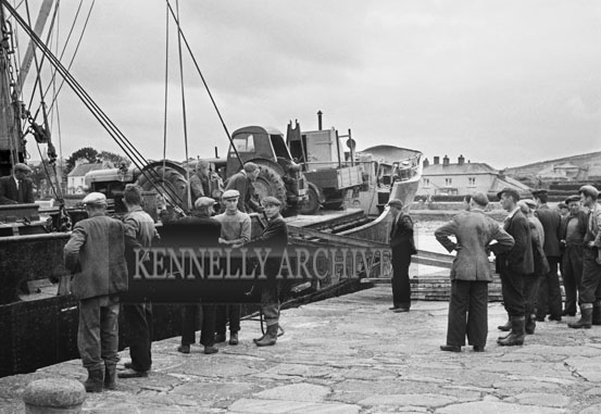 1953; Men Unloading Tractors From A Boat At Valentia Island Pier.