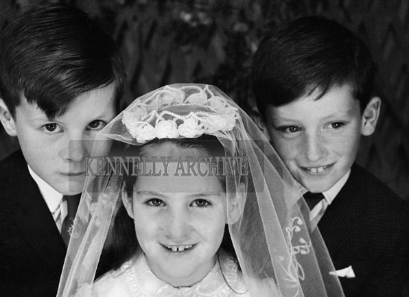 1953; A Studio Photo Of A Communion Boy And Girl Posing For The Camera With Another Boy.