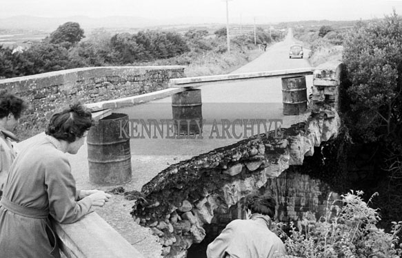 June 1957; A photo of a flood-damaged bridge.