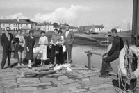 1953; Eamonn and Grainne Andrews (centre) Waiting For The Ferry On Valentia Island.