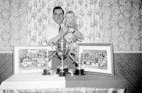 John Kissane and a Baby with Kerins O'Rahillys Trophies