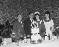 June 1964; A photo taken of a wedding couple and some of the wedding party at the reception held in the Hotel Manhattan.