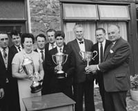 July 1964; Committee members of Dingle Festival with trophies presented by Messrs. Guinness for boat races at Dingle Regatta. L to R: John Sheehy, Pat Sheehy, Mrs James O'Keeffe (Festival Secretary); Frank Carroll (Joint Treasurer); Timothy J. Brosnan, Mr M. Begley, M.C.C. (Chairman Regatta Committee); James Ashe, (Guinness Agent), Michael Ashe, (Guinness Agent); P. Begley, (Guinness Representative).