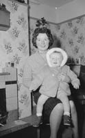 January 1964; A photo of a mother and a baby at a first birthday party.