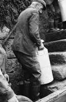 1953; A Man Carrying A Milk Churn Up The Steps After Unloading It From The Ferry On Valentia Island.