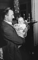 February 1954; A man holding a baby at home.