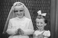 1953; A Studio Photo Of A Communion Girl And Her Sister Posing For The Camera.