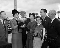 2nd September 1964; Rose of Tralee Margaret O'Keefe presents the Carling Rose Bowl to Mrs King-Harmon, owner of 'Bonne', the winner the Carling Black Label Stakes at Ballybeggan Park, Tralee. Jockey Johnny Roe is fifth from left in the photo.
