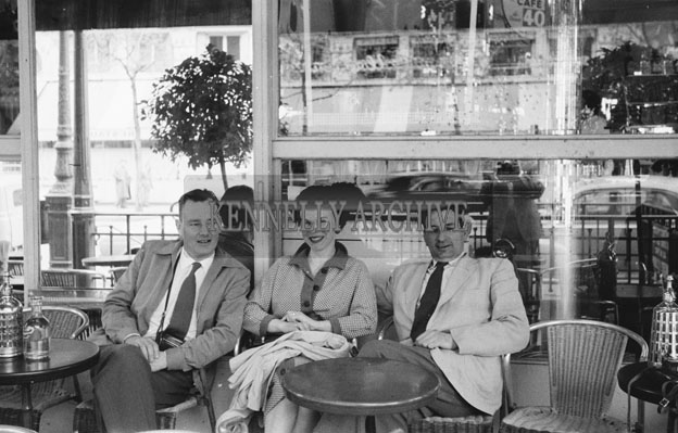 1953; Norman Ross of the Royal Hotel, Valentia (right) with a couple in a  Cafe in Paris, France.