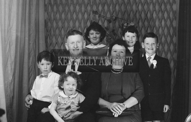 1953; A Studio Photo Of A Communion Boy Posing For The Camera With His Family.