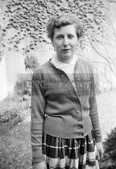 May 1957; A woman poses for the camera on confirmation day in Ballylongford.