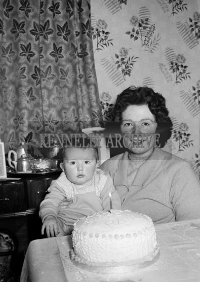 January 1964; A photo of a baby at home with his mother on his first birthday.