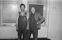 1953; Two Men Pose For The Camera Indoors On Valentia Island.