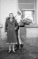 December 1957; A photo of a Santa visit to a school.
