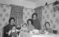 January 1964; A photo of a baby at home with his family on his first birthday.